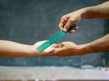 Teacher use the ruler hit the kid`s hand for punishment. Punish students royalty free stock photos