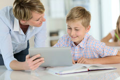 Teacher using digital tablet with pupil Royalty Free Stock Photos