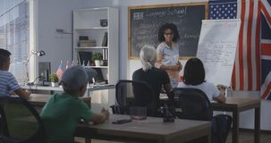 Teacher using flip chart while explaining to a class stock images
