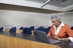 Teacher Using Laptop In Classroom Stock Image
