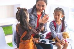 Teacher using tablet to tell little kid stories. Teacher using tablet e book to tell little kid stories stock images