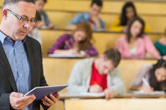 Teacher using tablet PC with students at lecture hall Stock Photography