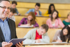 Teacher using tablet PC with students sitting at lecture hall Royalty Free Stock Images