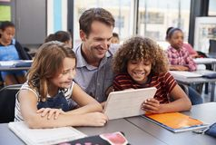 Teacher using tablet with two pupils in school class Royalty Free Stock Photos