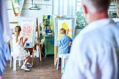 Teacher Watching Kids Painting in Art Studio. Back view portrait of senior teacher watching children painting on easels during art class in cozy studio decorated stock image