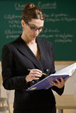 Teacher wearing eyeglasses reading text book Royalty Free Stock Photos