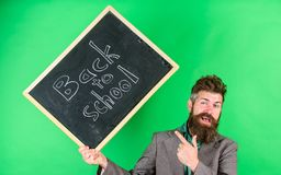 Teacher welcomes students while holds chalkboard inscription back to school. Teaching occupation demands talent and stock photos