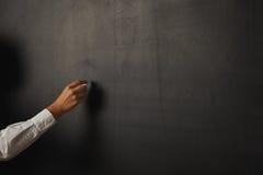 Teacher in white blouse at the blackboard Stock Photo
