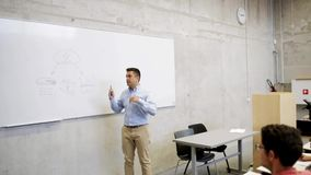 Teacher at white board and students on lecture stock footage