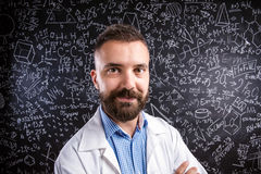 Teacher in white coat against big blackboard with mathematical s Stock Photos