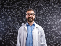 Teacher in white coat  and eyeglasses against big blackboard wit Royalty Free Stock Photo