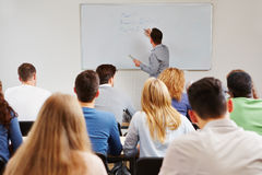 Teacher on whiteboard in class. Teaching business studies in university Stock Images