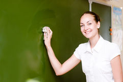 Teacher wipes the chalkboard. Young teacher wipes the chalkboard Royalty Free Stock Photo