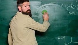 Teacher wiping chalkboard. School principal. Demanding teacher. Lecturer in classroom. Explaining theory. Teacher hold