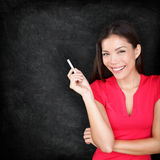 Teacher woman holding chalk by blackboard Stock Photos