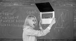 Teacher woman raising laptop above herself ready to destroy. Working conditions of teachers causes nervous disease. She. Needs pills to keep calm and mental royalty free stock images