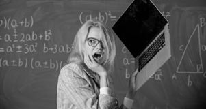 Teacher woman raising laptop above herself ready to destroy. Working conditions of teachers causes nervous disease. Overstrain of the nervous system. She needs royalty free stock images