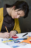 Teacher at work. A preschool teacher preparing some colorful cutouts for her young pupils Royalty Free Stock Image