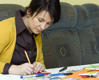 Teacher at work. A preschool teacher preparing some colorful cutouts for her young pupils Stock Photos