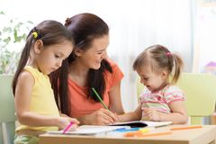Teacher working with children in preschool classroom. Teacher working with children kids in preschool classroom stock image