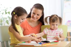 Teacher working with children in preschool classroom. Teacher working with children kids in preschool classroom stock images
