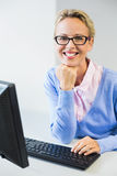 Teacher working on computer in classroom. Portrait of happy teacher working on computer in classroom at school Royalty Free Stock Image