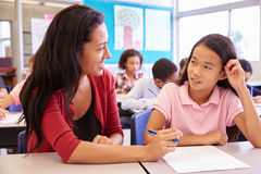 Teacher working with elementary school girl at her desk Royalty Free Stock Photo