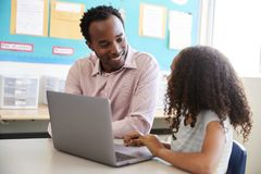 Teacher working with elementary school girl at laptop royalty free stock photo
