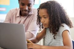 Teacher working with elementary school girl at laptop stock image