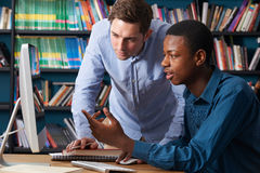 Teacher Working With Male Teenage Pupil At Computer Royalty Free Stock Photos