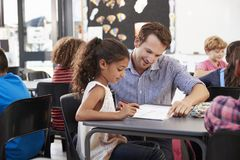 Teacher working with young schoolgirl at her desk in class Stock Images