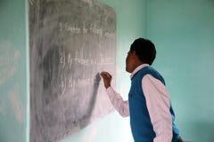 Teacher writes on blackboard Royalty Free Stock Image