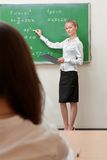 Teacher writes on blackboard Royalty Free Stock Images