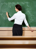 Teacher writes at the blackboard Royalty Free Stock Photography