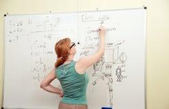 Teacher writes on blackboard Stock Image