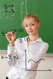 Teacher writes formula on glass Royalty Free Stock Photo