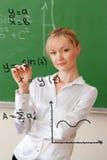 Teacher writes formula on glass Royalty Free Stock Photo