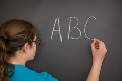 ABC. A teacher writing the ABC`s on the chalkboard Royalty Free Stock Images