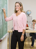 Teacher writing on blackboard Stock Photography
