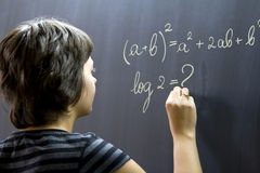 Teacher writing on blackboard. Teacher writing math formulas on blackboard Royalty Free Stock Image