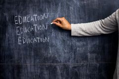 Teacher writing on blackboard Stock Image