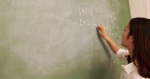 Teacher writing on blackboard. At elementary school stock footage