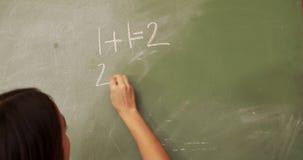 Teacher writing on blackboard. At elementary school stock video