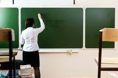 Teacher writing on the blackboard Royalty Free Stock Photo