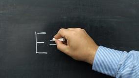 Teacher writing blackboard formula Einstein e=mc2 stock video footage