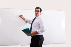 The teacher is writing on the blackboard. There is a lesson in school or university. The teacher looks in the classroom and smiles Stock Photo