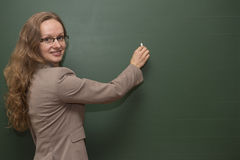 Teacher is writing on the board Stock Image