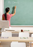 Teacher writing on chalk board in classroom Royalty Free Stock Photo