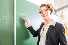Teacher writing with chalk in front of school class on board. Teacher or docent writing with chalk on the board or chalkboard or blackboard while math lesson in stock images