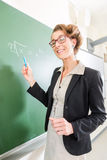 Teacher writing with chalk in front of school class on board Stock Photos